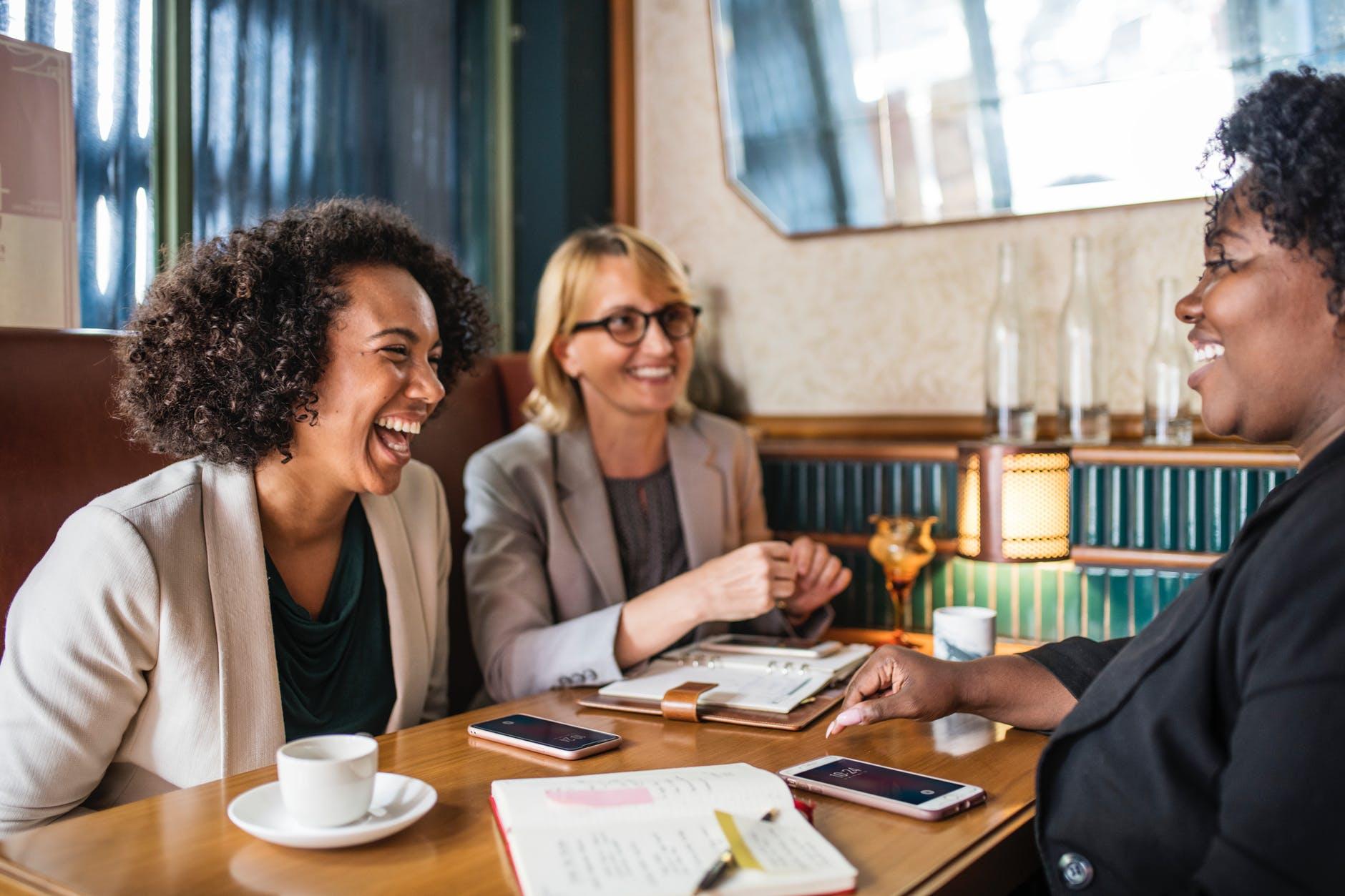 three woman sitting smiling inside room